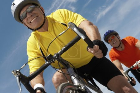 Men riding bicycles against sky