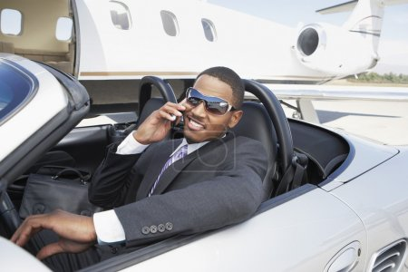 Young businessman using cell phone in convertible ...