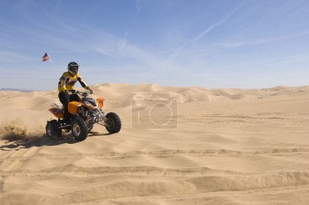 Man Riding ATV Over Sand Dune
