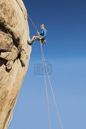Woman Rappelling on Cliff