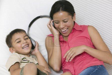 Photo pour Mère et fils couchés sur le canapé partageant les écouteurs - image libre de droit