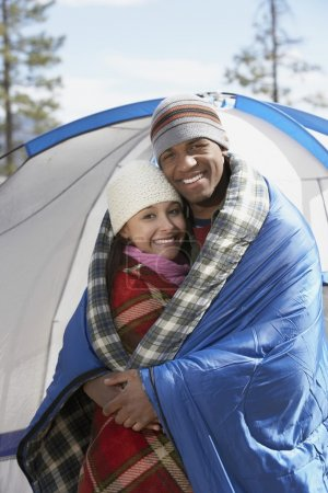 Couple wrapped in blankets at the campsite