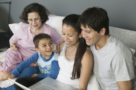 Family Using Laptop on Couch