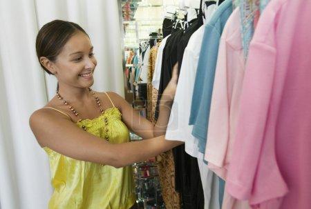 Woman Looking Through Clothing Rack