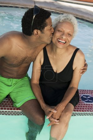 Man kissing mother at swimming pool