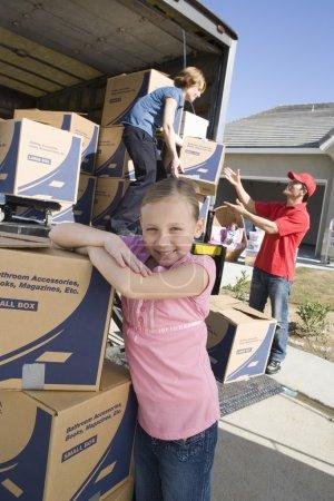 Photo pour Petite fille par camion de boîtes en carton - image libre de droit