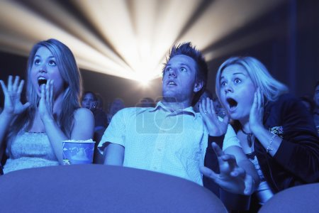 People watching horror movie in the theatre