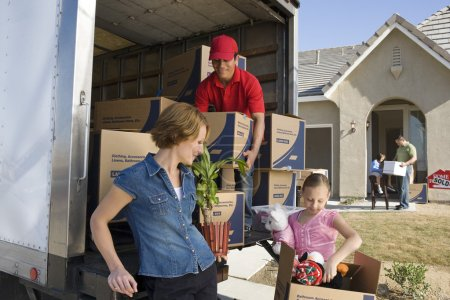 Photo for Family and worker unloading truck of cardboard boxes - Royalty Free Image