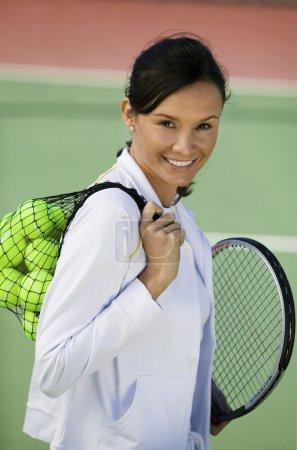 Woman with tennis balls and racket