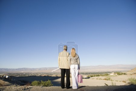Couple looking at plot for new home