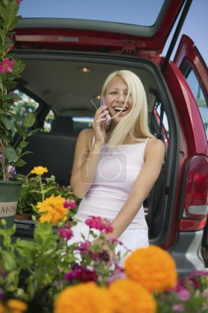 Woman with Phone at Plant Nursery