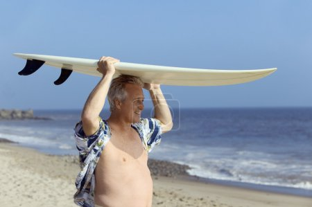 Male surfer carrying surfboard