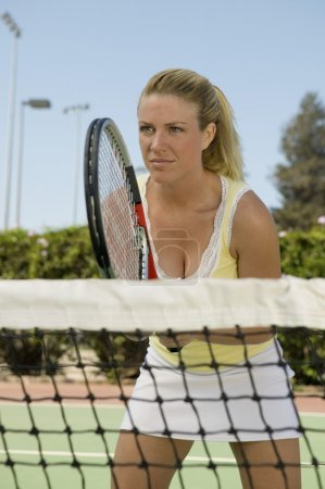 Woman standing at Tennis Net