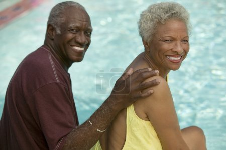 Photo for Senior Couple sitting by swimming pool - Royalty Free Image