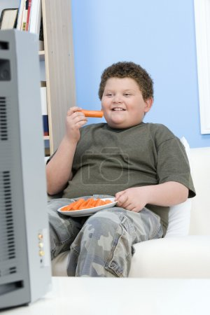 Overweight boy eating carrot