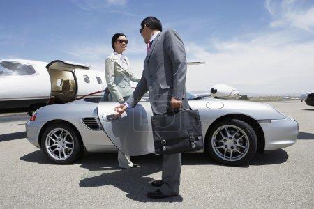 Businessman holding door of convertible for colleague