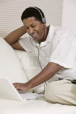 Man using laptop with headphones