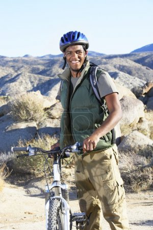Man standing with mountain bike