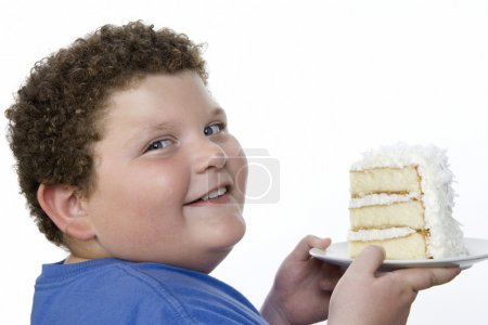 Overweight boy holding cake