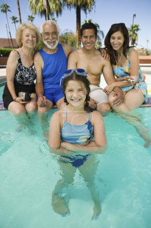 Girl with parents and grandparents at swimming poo...