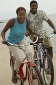 Couple cycling on beach