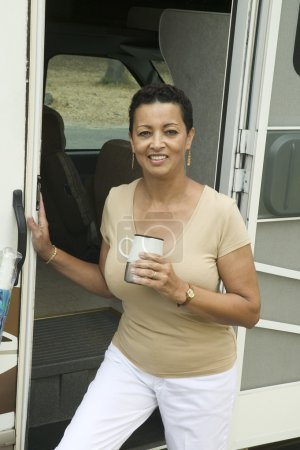 Woman with drink beside motor home