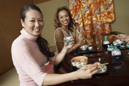 people holding saki cups