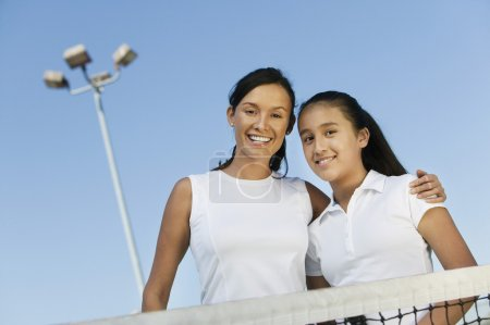 Mother and daughter on tennis court
