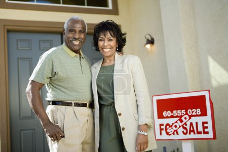 Couple standing by sold real estate sign