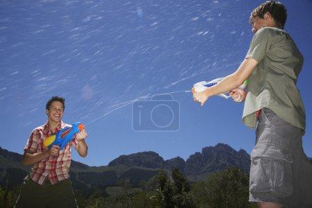 Jungen kämpfen mit Wasserpistolen