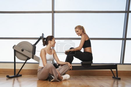 Photo for Two women talking at rowing machine in health club - Royalty Free Image