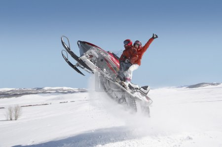 Couple jumping snowmobile
