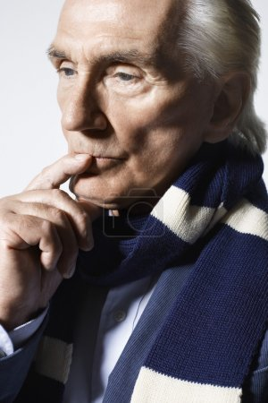 Closeup of a thoughtful senior man wearing scarf with finger on chin