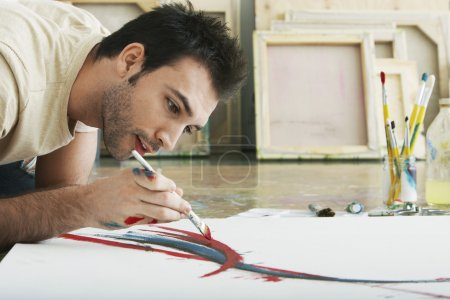 Photo for Man painting on canvas on studio floor - Royalty Free Image