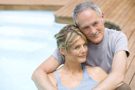 Couple sitting by swimming pool