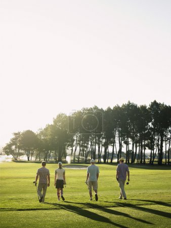 Golfers walking on golf course