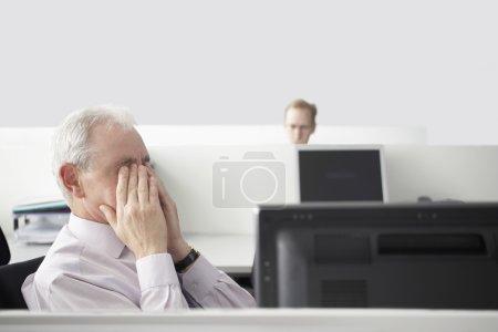 Mature businessman rubbing eyes