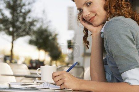Businesswoman writing at Sidewalk Cafe...