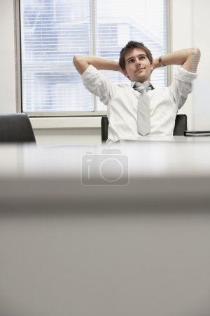 Businessman reclining in office chair