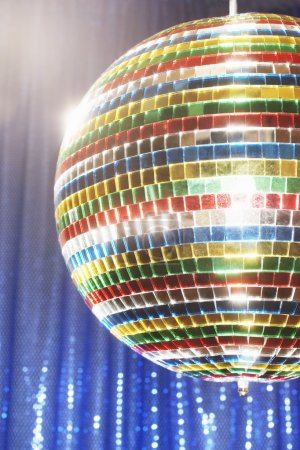 Photo for Multi-coloured disco ball in front of blue stage curtain cropped - Royalty Free Image