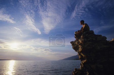 Photo for Man sitting on rock overlooking ocean - Royalty Free Image