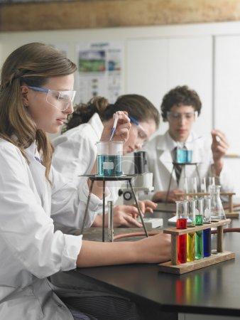 Photo pour Étudiants du secondaire utilisant des microscopes en classe - image libre de droit
