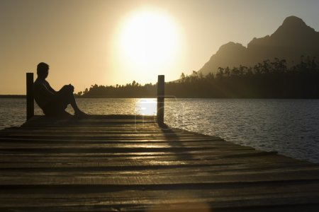 Photo for Man sitting on dock by lake side view. - Royalty Free Image