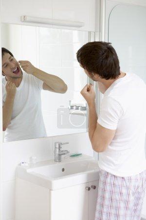 Photo pour Homme soie dentaire dents dans le miroir dans la salle de bain - image libre de droit