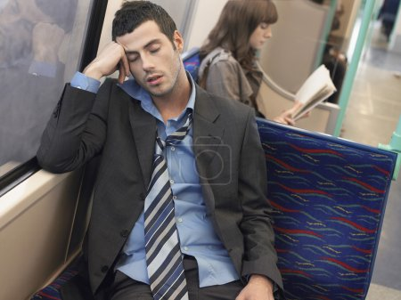 tired Businessman sleeping in  train