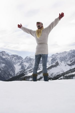 Photo for Rear view of a woman standing on mountain peak with arms outstretched - Royalty Free Image