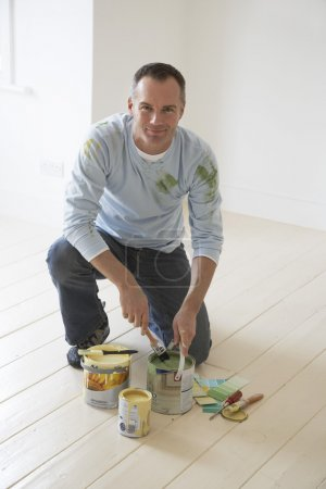 Photo for Man kneeling on floor with painting materials - Royalty Free Image