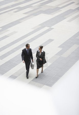 Businessman and businesswoman walking across