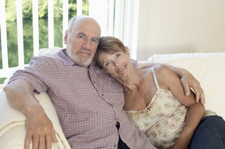 Middle Aged Couple sitting on sofa