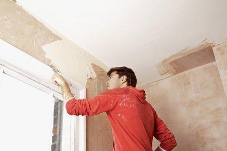 Photo pour Homme raclant la peinture sur le mur dans une pièce non rénovée vue à angle bas - image libre de droit
